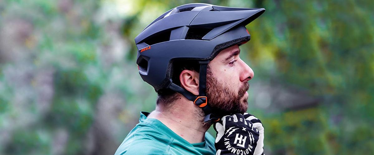 Cyclist securing mountain bike helmet on