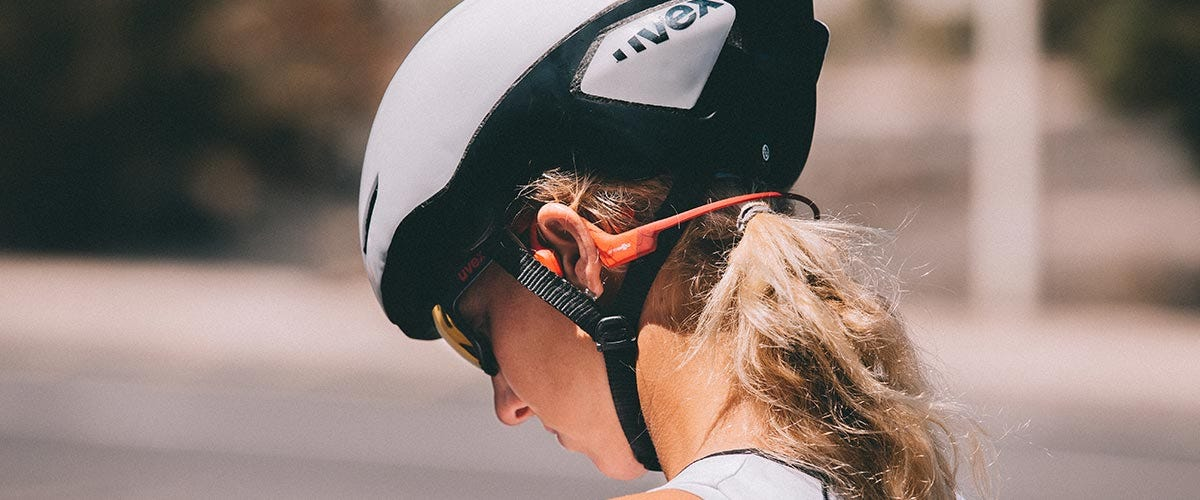 Cyclist riding bike with Aftershokz headphones one