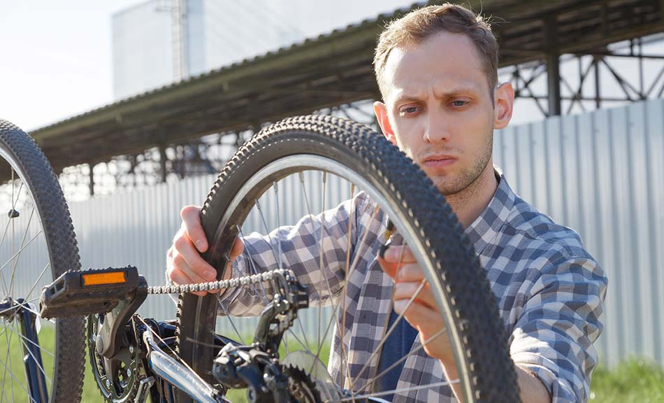 Cyclist inspecting bike tyre