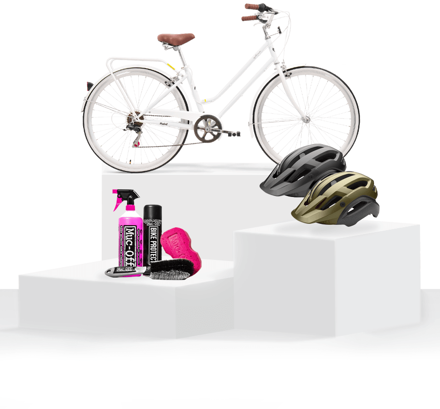 Pedestal of products - Pedal uptown cruiser bike white, 2x Giro manifest helmets black and green, plus Muc-Off Bike Care Essentials Kit