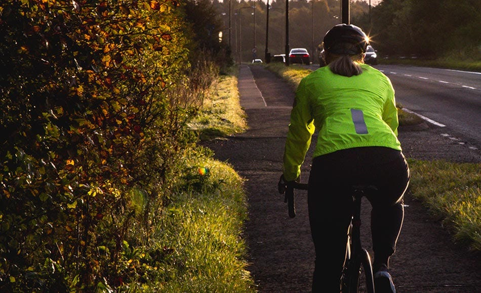 Woman riding bike home in late afternoon wearing high-visibility jacket