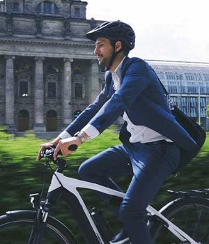 Commuter riding an electric bike in suit