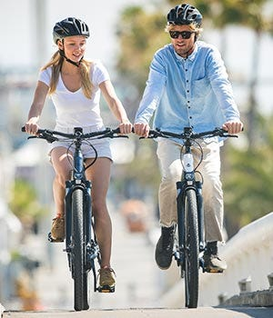 Young couple riding electric bikes together